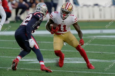 San Francisco 49ers wide receiver Brandon Aiyuk (11) runs after catching a pass as New England Patriots defensive back Devin McCourty (32) gives chase in the first half of an NFL football game, in Foxborough, Mass