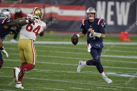 New England Patriots quarterback Jarrett Stidham rolls out to pass against the San Francisco 49ers in the second half of an NFL football game, in Foxborough, Mass