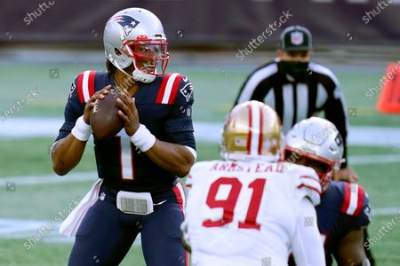 New England Patriots quarterback Cam Newton drops back to pass under pressure from San Francisco 49ers defensive end Arik Armstead (91) in the first half of an NFL football game, in Foxborough, Mass