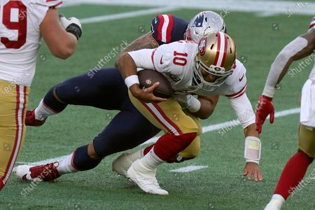 New England Patriots defensive lineman Lawrence Guy, rear, sacks San Francisco 49ers quarterback Jimmy Garoppolo in the first half of an NFL football game, in Foxborough, Mass