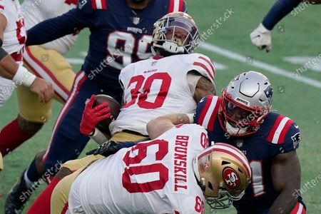 San Francisco 49ers running back Jeff Wilson Jr. (30) spins to gains yardage behind the block of tackle Daniel Brunskill (60) in the first half of an NFL football game against the New England Patriots, in Foxborough, Mass