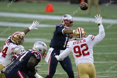 New England Patriots quarterback Cam Newton, rear, passes under pressure from San Francisco 49ers defenders Fred Warner (54) and Kerry Hyder Jr. (92) in the first half of an NFL football game, in Foxborough, Mass