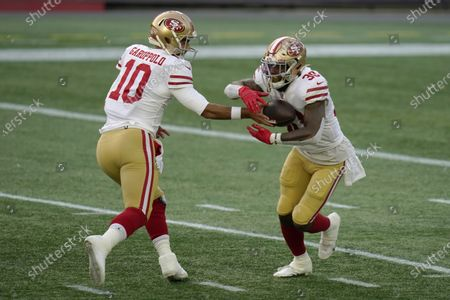 San Francisco 49ers quarterback Jimmy Garoppolo, left, hands off to running back Jeff Wilson Jr., in the first half of an NFL football game against the New England Patriots, in Foxborough, Mass