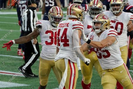 San Francisco 49ers fullback Kyle Juszczyk, center, celebrates his touchdown with teammates Jeff Wilson Jr., left, and George Kittle, right, in the first half of an NFL football game against the New England Patriots, in Foxborough, Mass