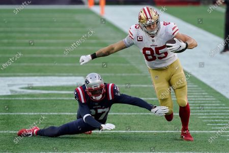 San Francisco 49ers tight end George Kittle (85) eludes New England Patriots defensive back J.C. Jackson (27) after catching a pass in the first half of an NFL football game, in Foxborough, Mass