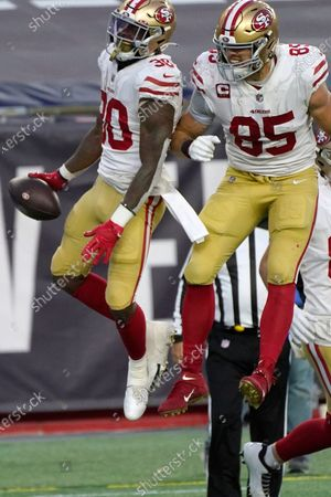 San Francisco 49ers running back Jeff Wilson Jr., left, celebrates his touchdown with George Kittle, right,in the first half of an NFL football game against the New England Patriots, in Foxborough, Mass