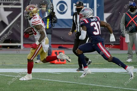San Francisco 49ers running back Jeff Wilson Jr., left, runs from New England Patriots defensive back Jonathan Jones (31) on his way to a touchdown in the first half of an NFL football game, in Foxborough, Mass