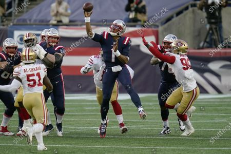 New England Patriots quarterback Cam Newton, center, passes under pressure from San Francisco 49ers linebacker Azeez Al-Shaair (51) and defensive end Dion Jordan, right, in the first half of an NFL football game, in Foxborough, Mass
