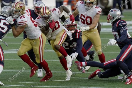 Stockafbeelding van San Francisco 49ers running back Jeff Wilson Jr. (30) runs from New England Patriots cornerback Stephon Gilmore (24) in the first half of an NFL football game, in Foxborough, Mass
