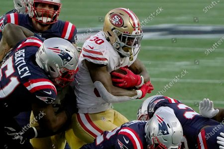 Stockafbeelding van New England Patriots linebacker Ja'Whaun Bentley (51) tackles San Francisco 49ers running back Jeff Wilson Jr. (30) in the first half of an NFL football game, in Foxborough, Mass