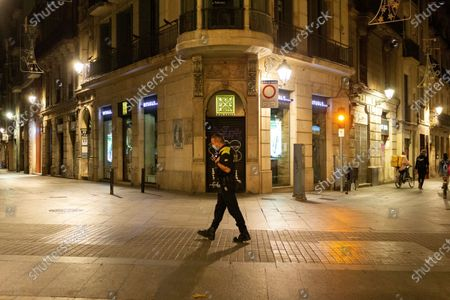 Illustration libre de droits de An Urban Guard walks on an oddly deserted Ramblas avenue in central Barcelona, Catalonia, Spain, 25 October 2020, after a new curfew from 10pm until 06 am. Spanish central government has declared new measures to stop the spreading of the coronavirus pandemic, including a national curfew from 11pm to 06 am allowing regional governments to make small amends on the timing.