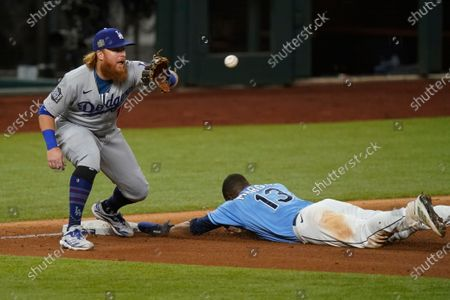 Tampa Bay Rays' Manuel Margot is safe at third past Los Angeles Dodgers third baseman Justin Turner after a Los Angeles Dodgers fielding error by Chris Taylor during the fourth inning in Game 5 of the baseball World Series, in Arlington, Texas