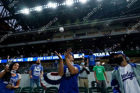 Los Angeles Dodgers fans try to catch a ball during batting practice before Game 5 of the baseball World Series against the Tampa Bay Rays, in Arlington, Texas