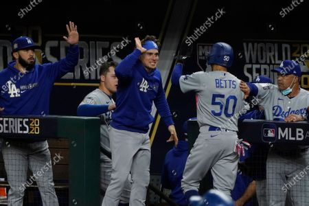 Los Angeles Dodgers' Mookie Betts celebrates at the dugout after scoring on a hit by Corey Seager during the first inning in Game 5 of the baseball World Series against the Tampa Bay Rays, in Arlington, Texas