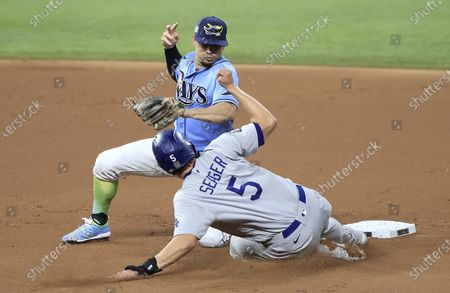 Los Angeles Dodgers baserunner Corey Seager (R) is safe at second base advancing on a wild pitch as Tampa Bay Rays shortstop Willy Adames (L) puts down the tag too late in the top of the first inning of Major League Baseball's World Series Game five at Globe Life Field in Arlington, Texas, USA, 25 October 2020. The best-of-seven series is tied 2-2.