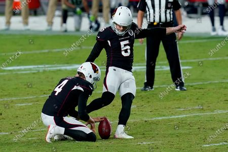 Arizona Cardinals kicker Zane Gonzalez (5) kicks the game winning field goal as punter Andy Lee (4) holds during the second half of an NFL football game against the Seattle Seahawks, in Glendale, Ariz. The Cardinals won 37-34 in overtime