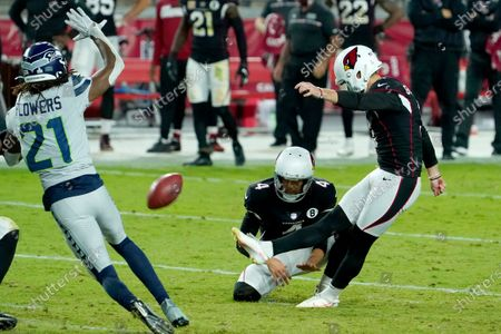 Arizona Cardinals kicker Zane Gonzalez kicks the game winning field goal as punter Andy Lee (4) holds during the second half of an NFL football game against the Seattle Seahawks, in Glendale, Ariz. The Cardinals won 37-34 in overtime