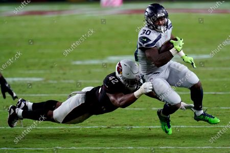 Seattle Seahawks running back Carlos Hyde (30) is hit by Arizona Cardinals outside linebacker Devon Kennard (42) during the second half of an NFL football game, in Glendale, Ariz