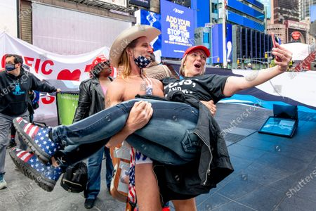 Robert John Burck AKA Naked Cowboy attends while playing a guitar with Trump Stickers as Trump Supprters march in Times Square