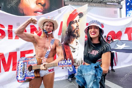 """Robert John Burck AKA Naked Cowboy poses with a woman holding a sign depicting Jesus with a """"Make America Great Again"""" hat while playing a guitar with Trump Stickers as Trump Supprters march in Times Square"""