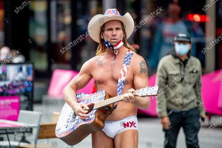 Stock Picture of Robert John Burck AKA Naked Cowboy attends while playing a guitar with Trump Stickers as Trump Supprters march in Times Square
