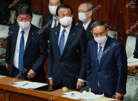Japanese Prime Minister Yoshihide Suga (R) stands with Finance Minister Taro Aso (C) and Foreign Minister Toshimitsu Motegi (L) before delivering his policy speech during the extraordinary parliament session at the Upper House in Tokyo, Japan, 26 October 2020.