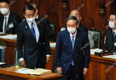 Japanese Prime Minister Yoshihide Suga (R) leaves his seat with Finance Minister Taro (L) Aso after delivering his policy speech during the extraordinary parliament session at the Upper House in Tokyo, Japan, 26 October 2020.