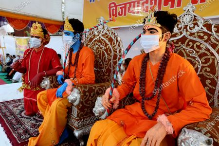 Stock Photo of Men dressed as Lord Rama (C), his brother Laxmana (R) and Lord Hanumaan wear a protective face mask during Dussehra festival celebrations in Bhopal, India, 26 October 2020. Limited people were allowed inside the Dussehra festival area due to Indian government guidelines over the Covid-19 pandemic. Dussehra is an annual Hindu festival, which follows the nine-day festival of Navratri and marks the victory of the mythological Hindu God Lord Rama over the evil demon king Ravana.