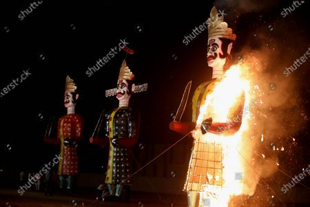 Stock Picture of Effigies of demon king Ravana (C), Meghnath (L) and Kumbhakarana burn during Dussehra festival celebrations in Bhopal, India, 26 October 2020. Limited people were allowed inside the Dussehra festival area due to Indian government guidelines over the Covid-19 pandemic. Dussehra is an annual Hindu festival, which follows the nine-day festival of Navratri and marks the victory of the mythological Hindu God Lord Rama over the evil demon king Ravana.