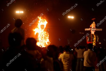 Stock Image of An effigy of Hindu figure Meghnath burns next to a statue of demon king Ravana (R) during Dussehra festival celebrations in Bhopal, India, 26 October 2020. Limited people were allowed inside the Dussehra festival area due to Indian government guidelines over the Covid-19 pandemic. Dussehra is an annual Hindu festival, which follows the nine-day festival of Navratri and marks the victory of the mythological Hindu God Lord Rama over the evil demon king Ravana.