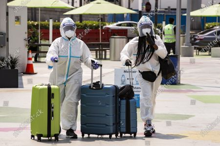 YEARENDER 2020  ECONOMY BUSINESS FINANCE  Two passengers in full protective gear push their luggage as they arrive in the rideshare zone of the LAX Airport to catch a ride in Los Angeles, California, USA, 20 August 2020.