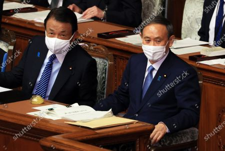 Japanese Prime Minister Yoshihide Suga (R) and Finance Ministedr Taro Aso (L) arrive at the plenary session of Lower House as Suga delivers his policy speech at the National Diet in Tokyo on Monday, October 26, 2020. Suga pledged to cut greenhouse gas emission to net zero by 2050 in Japan.