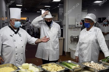 Britain's Prime Minister Boris Johnson, center, and Great British Bake Off judge Prue Leith speak to a chef during a visit to Royal Berkshire Hospital, Reading, England, to mark the publication of a new review into hospital food