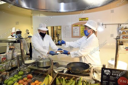 Britain's Prime Minister Boris Johnson, left, Great British Bake Off judge Prue Leith serve up a meal during a visit to Royal Berkshire Hospital, Reading, England, to mark the publication of a new review into hospital food