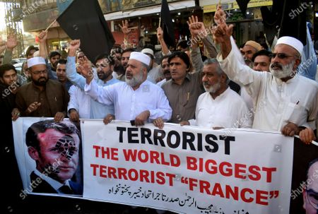 Pakistan traders hold a banner with a defaced picture of French President Emmanuel Macron during a protest against the publishing of caricatures of the Prophet Muhammad they deem blasphemous, in Peshawar, Pakistan, . Pakistan's Prime Minister Imran Khan said the French leader chose to encourage anti-Muslim sentiment and deliberately provoke Muslims by encouraging the display of blasphemous cartoons targeting Islam
