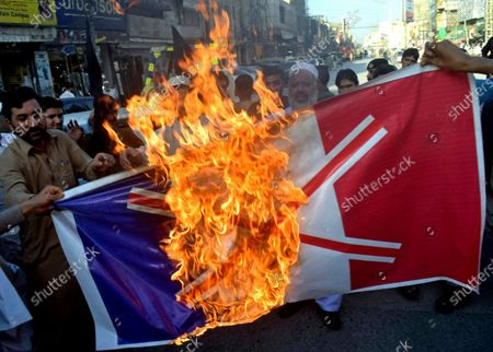 Pakistan traders burn burn a representation of the French flag during a protest against the publishing of caricatures of the Prophet Muhammad they deem blasphemous, in Peshawar, Pakistan, . Pakistan's Prime Minister Imran Khan said the French leader chose to encourage anti-Muslim sentiment and deliberately provoke Muslims by encouraging the display of blasphemous cartoons targeting Islam