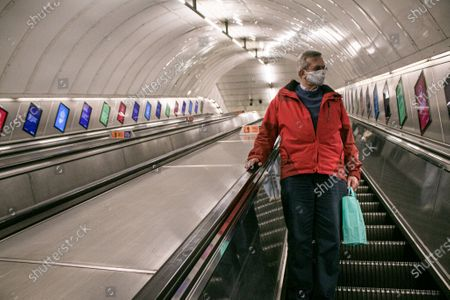 A man standing in an escalator. Passenger numbers remain down on the London Underground and trains are  not busy particularly at rush hour.  as the government imposes tighter Coronavirus covid 19.  Members of the public are required to wear face coverings which has become mandatory on public tranport where social distancing is not possible