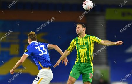 Brighton's Dan Burn, left, and West Bromwich Albion's Branislav Ivanovic challenge for the ball during the English Premier League soccer match between Brighton and West Bromwich Albion at the American Express Community Stadium in Brighton, England