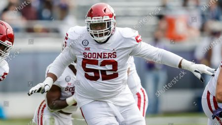 Oklahoma offensive lineman Tyrese Robinson (52) protects quarterback Spencer Rattler during an NCAA college football game against TCU, in Fort Worth, Texas. Oklahoma won 33-14