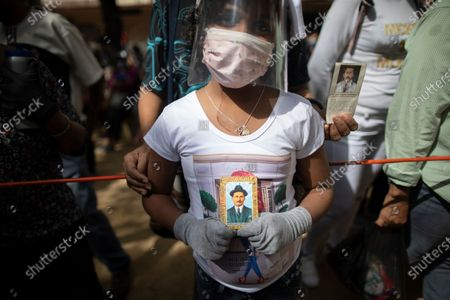"Stock Photo of Mari Carmen Centeno, 10, who said she'd been operated on for a head tumor, holds an image of late Venezuelan Dr. Jose Gregorio Hernández outside La Candelaria church where he is buried in Caracas, Venezuela, . The remains of the doctor popularly known as the ""Saint of the Poor"" were exhumed today in a private ceremony inside the church as part of a Vatican request for the beatification process of the first Venezuelan layperson"