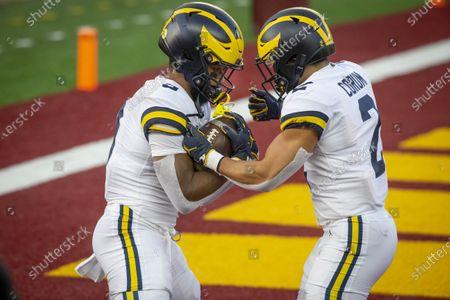 Michigan running backs Chris Evans (9) and Blake Corum (2) run drills to prepare for an NCAA college football game with Minnesota, in Minneapolis. Michigan won 49-24