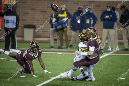 Michigan linebacker Michael Barrett (23) knock the ball loose from Minnesota quarterback Tanner Morgan (2) as Mohamed Ibrahim (24) watches in the first quarter of an NCAA college football game, in Minneapolis. The ball was caught by Michigan defensive lineman Donovan Jeter (95) and returned for a touchdown. Michigan won 49-24
