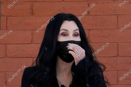Iconic singer Cher adjusts her face covering as she speaks near a polling station while campaigning for Democratic presidential candidate Joe Biden, in Phoenix