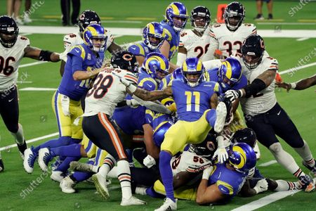 Los Angeles Rams players try to push running back Malcolm Brown into the end zone during the second half of an NFL football game against the Chicago Bears, in Inglewood, Calif