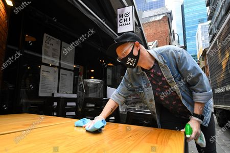 Patrick Walsh, staff member of Hochi Mama restaurant sanitises a table in preparation to reopen the restaurant in Melbourne, Victoria, Australia, 27 October 2020. Victorian Premier Daniel Andrews has confirmed a major easing of Melbourne's coronavirus restrictions as a northern suburbs outbreak is brought under control.