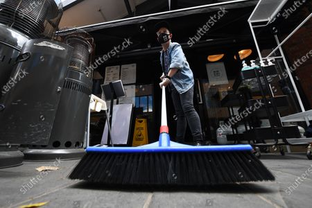Stock Image of Patrick Walsh, staff member of Hochi Mama restaurant sweeps the footpath in preparation to reopen the restaurant in Melbourne, Victoria, Australia, 27 October 2020. Victorian Premier Daniel Andrews has confirmed a major easing of Melbourne's coronavirus restrictions as a northern suburbs outbreak is brought under control.