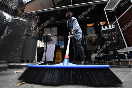 Stock Photo of Patrick Walsh, staff member of Hochi Mama restaurant sweeps the footpath in preparation to reopen the restaurant in Melbourne, Victoria, Australia, 27 October 2020. Victorian Premier Daniel Andrews has confirmed a major easing of Melbourne's coronavirus restrictions as a northern suburbs outbreak is brought under control.