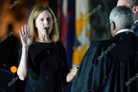 Supreme Court Justice Clarence Thomas administers the Constitutional Oath to Amy Coney Barrett on the South Lawn of the White House in Washington, after Barrett was confirmed by the Senate earlier in the evening. Jesse Barrett holds the Bible