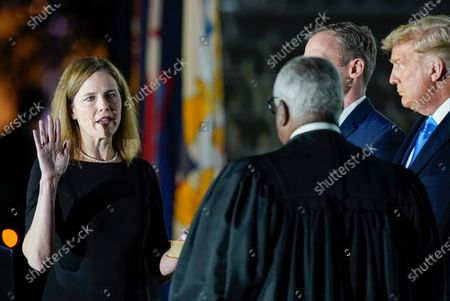 President Donald Trump watches as Supreme Court Justice Clarence Thomas administers the Constitutional Oath to Amy Coney Barrett on the South Lawn of the White House White House in Washington, after Barrett was confirmed to be a Supreme Court justice by the Senate earlier in the evening. Holding the Bible is Barrett's husband, Jesse Barrett