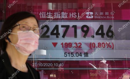 Woman walks past a bank's electronic board showing the Hong Kong share index at Hong Kong Stock Exchange . Shares skidded in Asia on Tuesday after surging coronavirus cases and waning hopes for U.S. economic stimulus gave Wall Street its worst day in a month